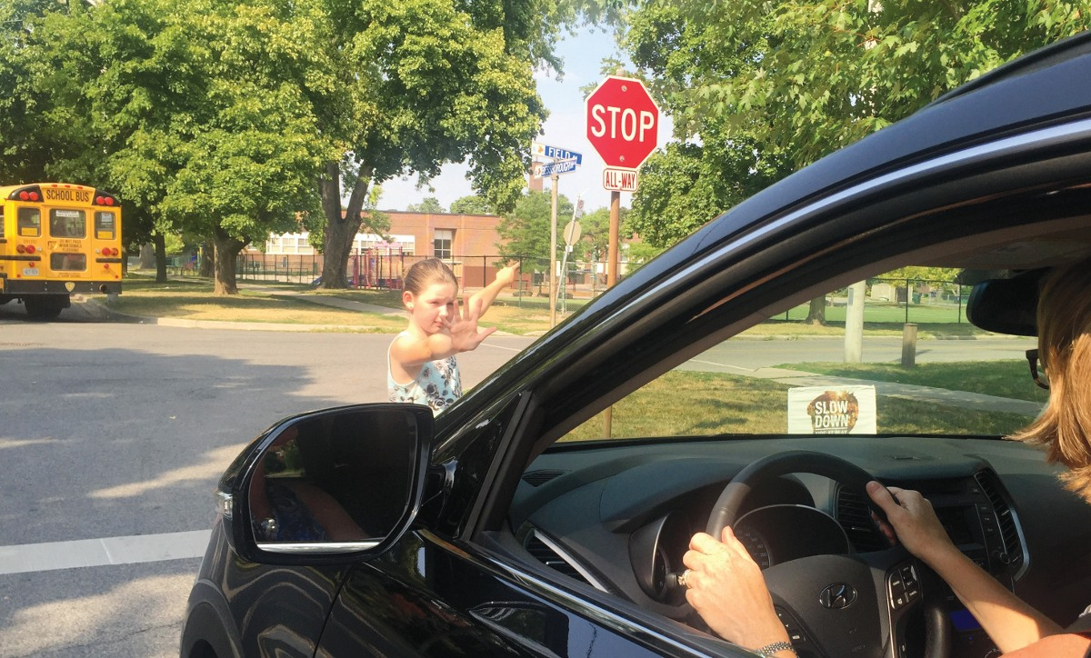 Anika Brophy reminds a driver near Bessborough school to slow down and stop.