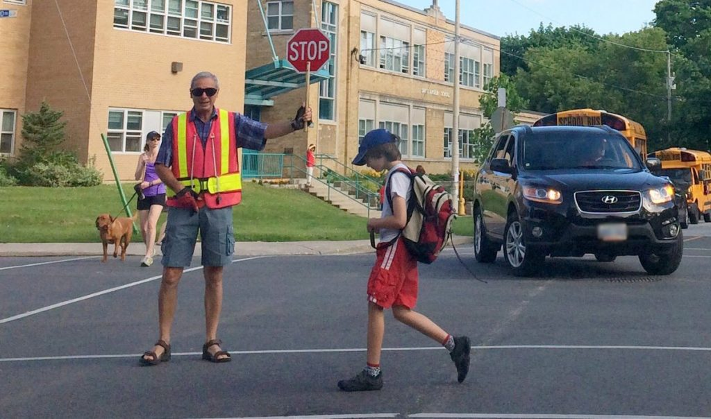 Crossing guard, Boris Cherkassky stops traffic at Millwood and Bessborough for St. Anselm's student Chris Karnay Gayowsky.
