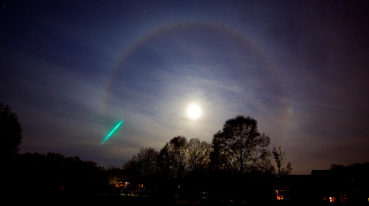 This a photo of a meteorite and a Moonbow around a Hunter's Moon. A moonbow is technically known as a 22? moon halo. The 22? Moon Halo is formed when moonlight passes through ice crystals in the atmosphere and are refracted approximately 22?.