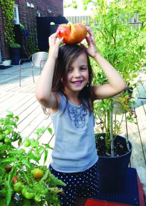 Mia shows off fruits of the roof garden.