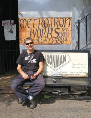 "Tom Mourgas the ""Iron Man"" outside his shop on Canvarco. Photo by Karli Vezina"