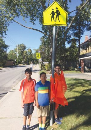 Arnav, Oliver and Quinlan with their orange flags. Photo By Janis Fertuck.