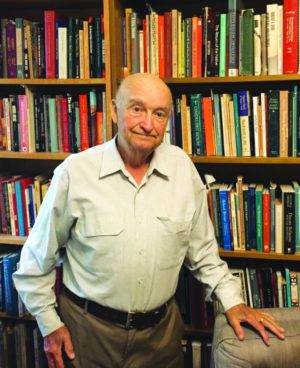 Professor Emeritus, Peter Russell, in his home library. Photo By Allan Williams.