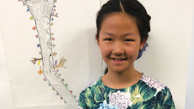 Vita Huang, 10, with her first prize drawing.