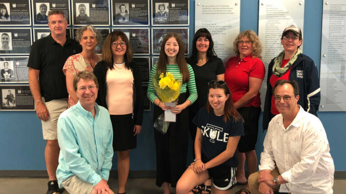 Back row l-r: board member Andrew Smyth, board president Jennifer Smith, Erin Parsons' mom Miah, Erin, board member Erin Loft, board member Beth Brotherstone, and Jenny Shaw. Front: Erin's dad Jeff, sister Moranne, and board member Mark Schrutt.