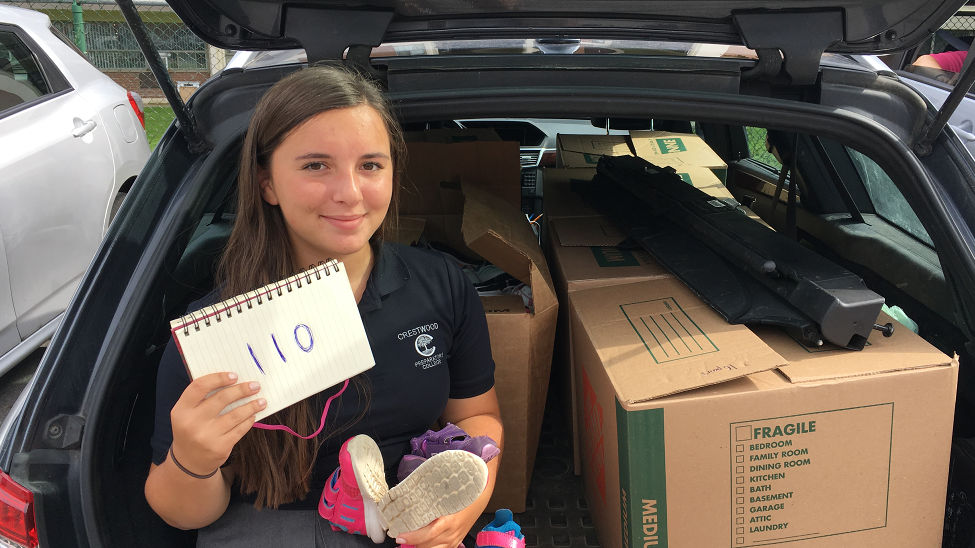 Caroline with her collection of 110 donated pairs of shoes.