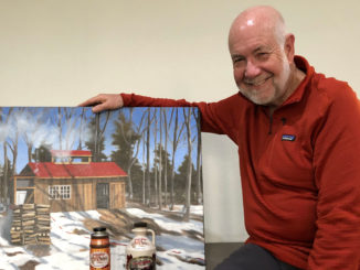 Larry with his maple syrup and a painting of the Sugar Shack by Graham Lute.